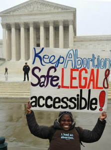 "smiling woman wearing t-shirt that says ""I had an abortion"", holding a sign that reads ""Keep abortion safe, legal, & accessible."""