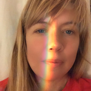 Photo of a blond woman in a red shirt with a beam of sunlight on her face
