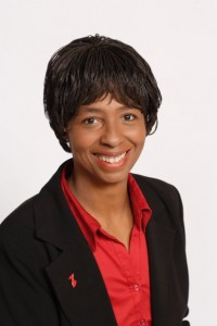 Portrait of Leslie Gregory, a Black woman wearing a red blouse and black jacket.