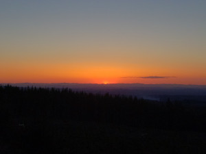 The setting sun meets the dark horizon in the middle distance filling the upper portion of the image with a gradient that moves from smouldering orange to muddy water