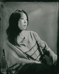 Black and white photo of a woman with dark hair sitting in a chair