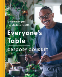 Book cover for Everyone's Table cookbook showing author/chef Gourdet tossing a salad in a plant filled kitchen.