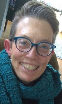 Smiling white woman with short gray hair, blue glasses, and a blue scarf