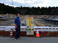 """Takeshi Yamakawa of Tokyo Shimbun stands next to a sign on Route 253 near Namie that says, """"Exclusion zone: do not enter.""""  A mega-solar farm built on abandoned farms is on the other side of the highway fence.  (Photo courtesy of U.G. Kaneko)"""